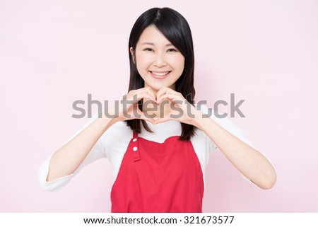 young housewife with apron showing hand heart gesture against pink background - stock photo