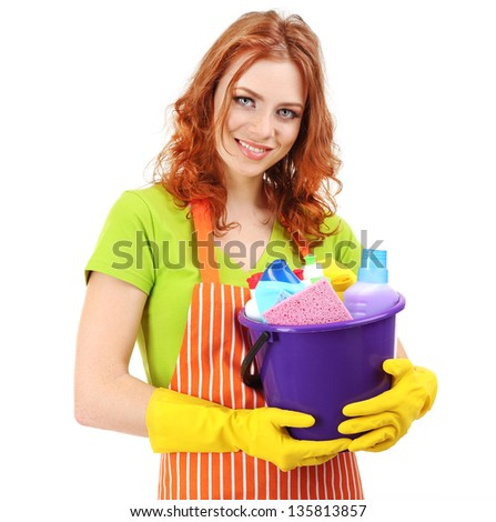 Young housewife with bucket of cleaning supplies, isolated on white - stock photo