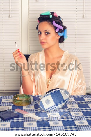 Young housewife with curlers in her hair smoking cigarette in the kitchen. - stock photo