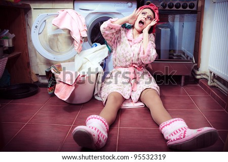 young housewife with washing machine and towels. - stock photo