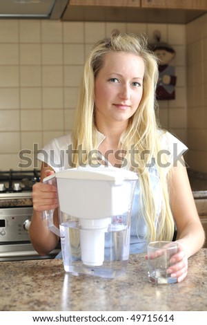 Young housewife with water jug - stock photo