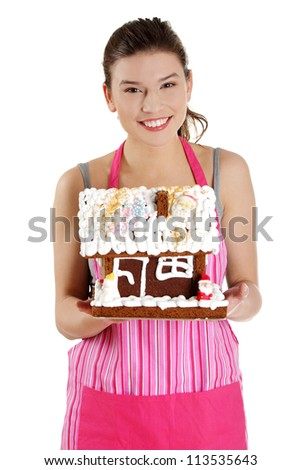 Young housewife woman in apron holding gingerbread house model, isolated on white background - stock photo