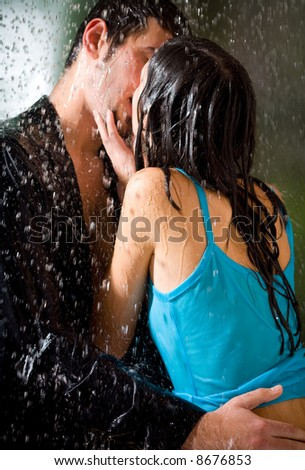 Young hugging couple kissing under a rain, in passion - stock photo