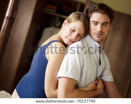 young husband and wife sitting on bed and hugging. Horizontal shape, waist up, side view - stock photo