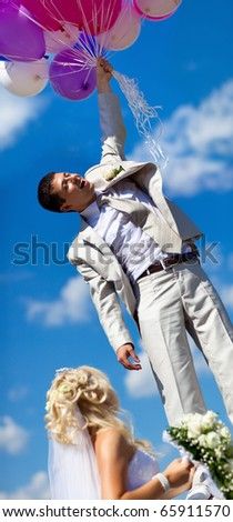 Young husband flying from his wife. Funny wedding concept. - stock photo