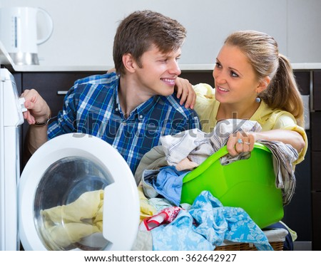 Young husband helping happy wife to use washing machine at home kitchen - stock photo