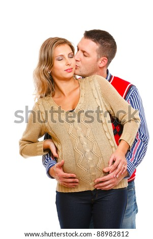 Young husband kissing his pregnant wife  on white background - stock photo