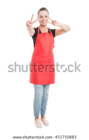 Young hypermarket saleswoman in red apron doing double peace gesture isolated on white studio background - stock photo
