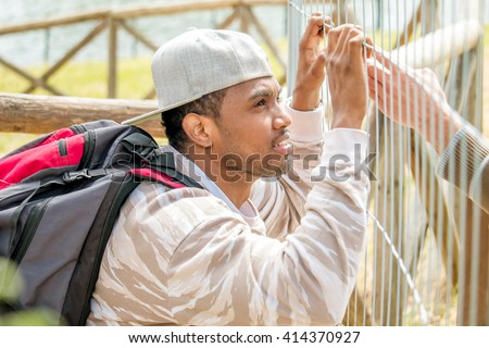 young immigrant holding metal barricade - hand of immigration officer speaking with asylum seeker seeking to cross border enter the country - concept of  illegal immigration and  refugee crisis - stock photo