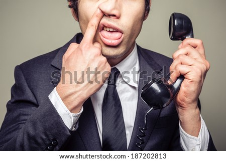 Young incompetent businessman is on the phone and is picking his nose - stock photo