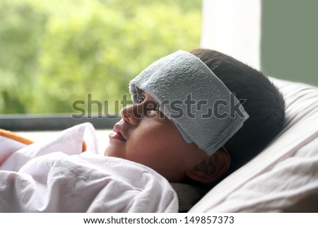 Young indian boy ( child ) down with fever & illness in hospital. A wet cloth is kept on forehead to reduce the temperature - stock photo