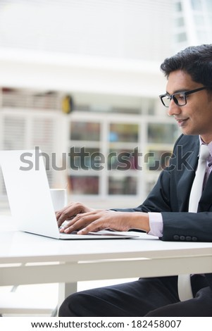 young indian business man on laptop and coffee at a cafe - stock photo