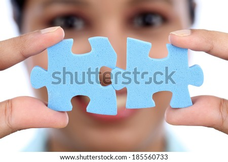 Young Indian business woman joining two jigsaw puzzle pieces against white background - stock photo