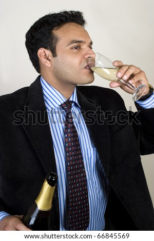 young Indian businessman drinking wine - stock photo