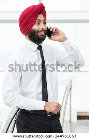 Young indian businessman in modern office is talking by phone. - stock photo