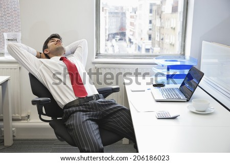 Young Indian businessman relaxing in chair at office desk - stock photo