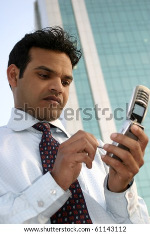 Young Indian Businessman using a mobile phone standing outside a modern office building - stock photo