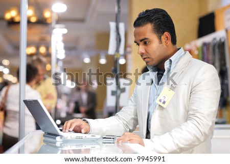Young indian businessman using laptop computer at trade show. - stock photo