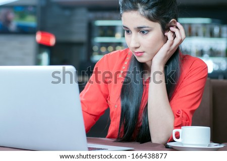 Young indian businesswoman on a coffee break. Using tablet computer. - stock photo