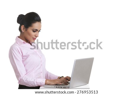 Young Indian businesswoman using laptop over white background - stock photo