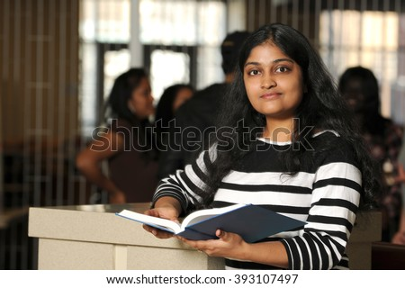 Young Indian college student holding book inside campus - stock photo