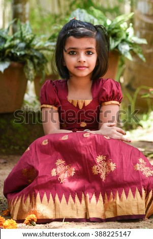 young Indian girl / child / kids wearing traditional dress for Onam, Vishu Kerala India . Asian child. Beautiful daughter in traditional Indian sari sitting down in park - stock photo