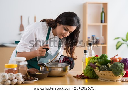 Young Indian housewife looking into a saucepan - stock photo