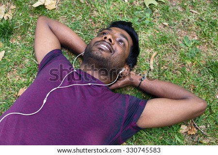 young indian man relaxing in the park listening to music - stock photo