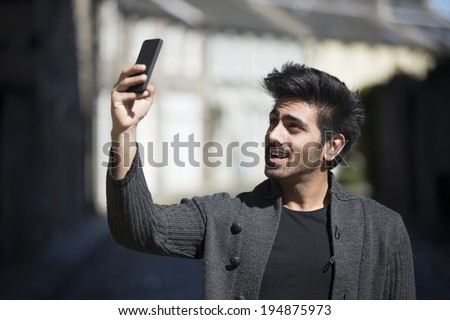Young Indian Man standing in city street taking a selfie, self-portrait photograph with mobile phone. Background is blured city. - stock photo