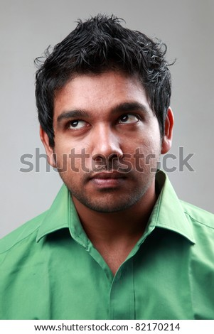 Young Indian man with eyes looking up - stock photo
