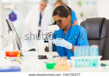 young indian medical researcher looking through microscope in laboratory - stock photo
