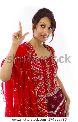 Young Indian woman pointing upward and smiling - stock photo