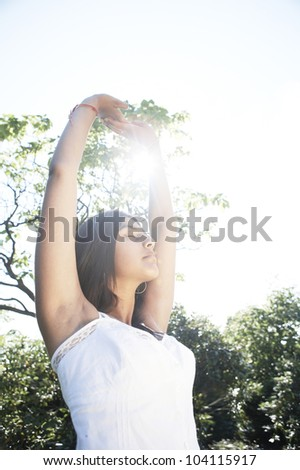 Young indian woman stretching and doing yoga in the park with the sun filtering through her arms. - stock photo