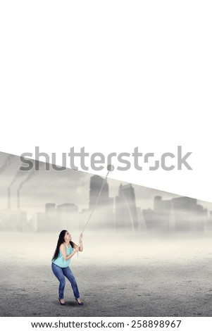 Young indian woman try to pull empty copyspace for environment campaign with air pollution background - stock photo