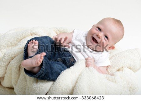 Young infant laughing hard while wearing jeans and a white shirt - stock photo