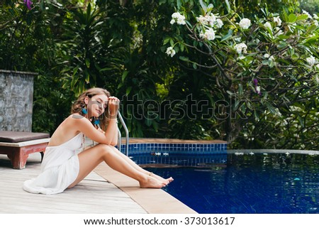 young innocent pure beautiful woman dreaming, sitting at pool in white dress, romantic, lyrical, thinking, green tropical nature, summer, relaxed, chilling, long legs - stock photo