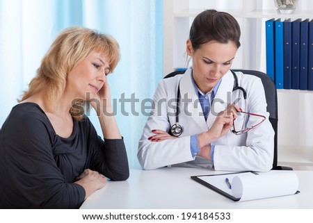 Young internist having bad news for a female patient - stock photo