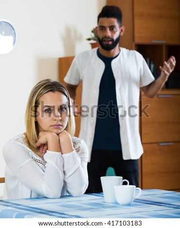 Young interracial family couple with serious faces arguing at home - stock photo