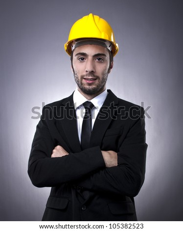 Young investor in black suit with yellow construction helmet posing with arms crossed - stock photo