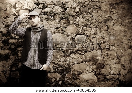 Young italian man against stone wall - stock photo