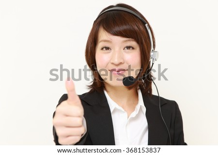 young Japanese businesswoman of call center with thumbs up gesture - stock photo