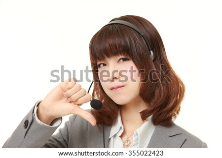 young Japanese businesswoman with thumbs down gesture - stock photo