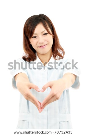 Young japanese female nurse shows fingers heart symbol - stock photo