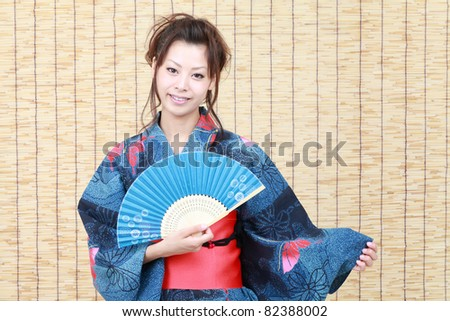 Young japanese woman in traditional clothes of kimono with japanese fan - stock photo
