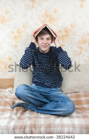 young joy student readig book on sofa at home - stock photo