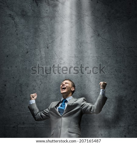 Young joyful businessman screaming with hands up - stock photo