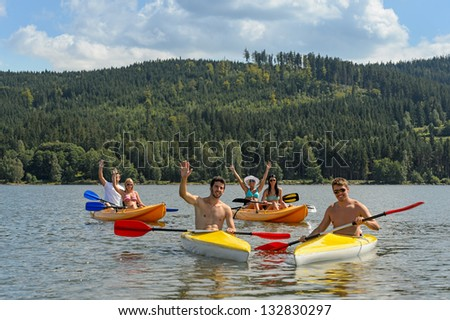 Young kayaking friends having fun in scenic view summer holiday - stock photo