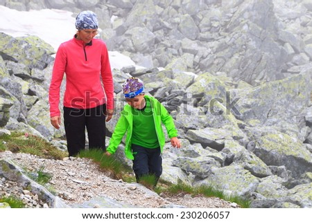 Young kid and mother climbs a rocky mountain side in foggy weather - stock photo