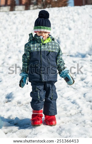 Young kid having fun in the snow. Full body portrait. - stock photo