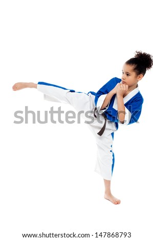 Young kid kicking in the air while practicing karate - stock photo